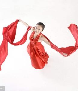 舞动红绸带的红裙美女